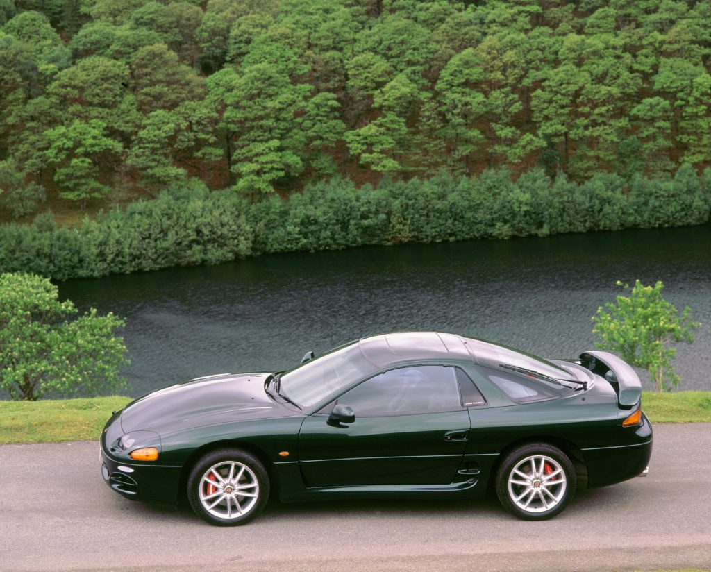 A green 1999 Mitsubishi 3000 GT is parked by a resevoir.