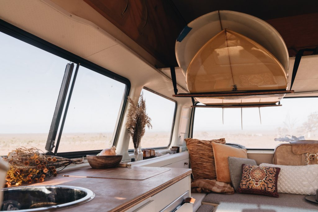 a view of old VW van Marty's interior with surfboards hung from the ceiling and lovely textured pillows in every shade of retro