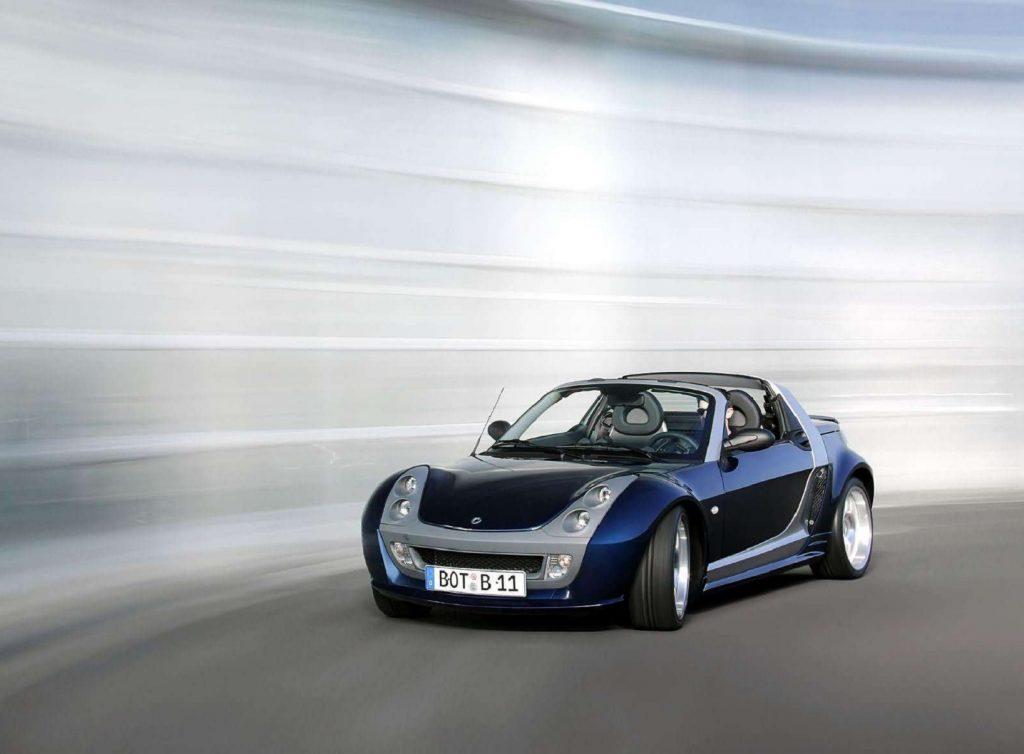 A blue 2003 Brabus Smart Roadster drives around a corner