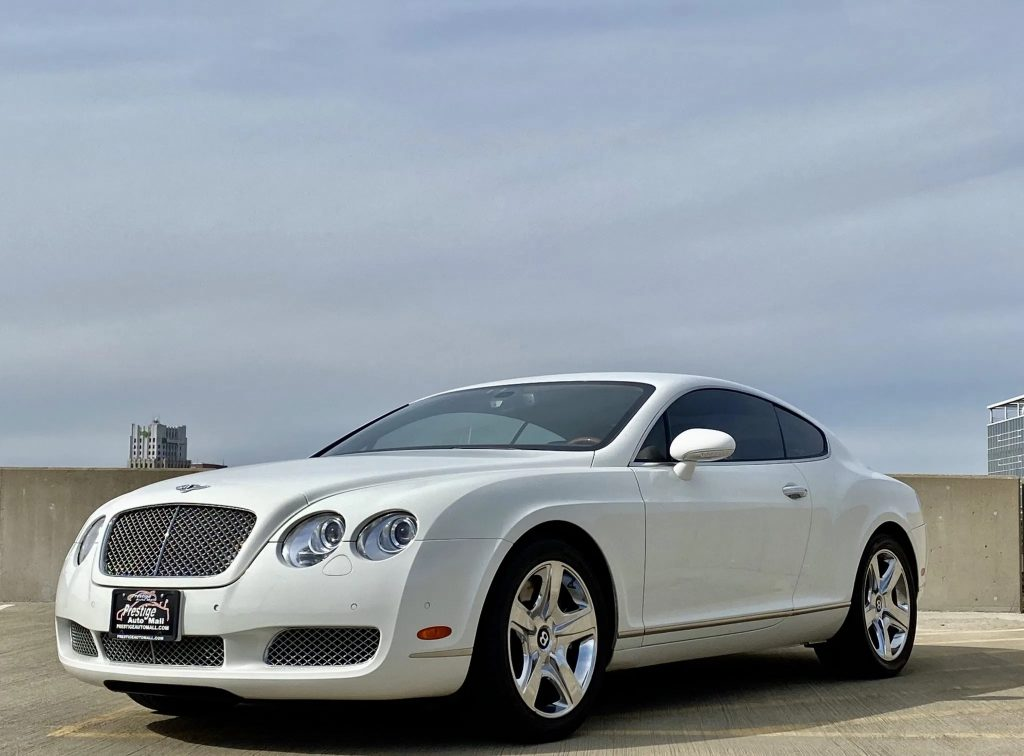 A white 2007 Bentley Continental GT on top of a parking garage