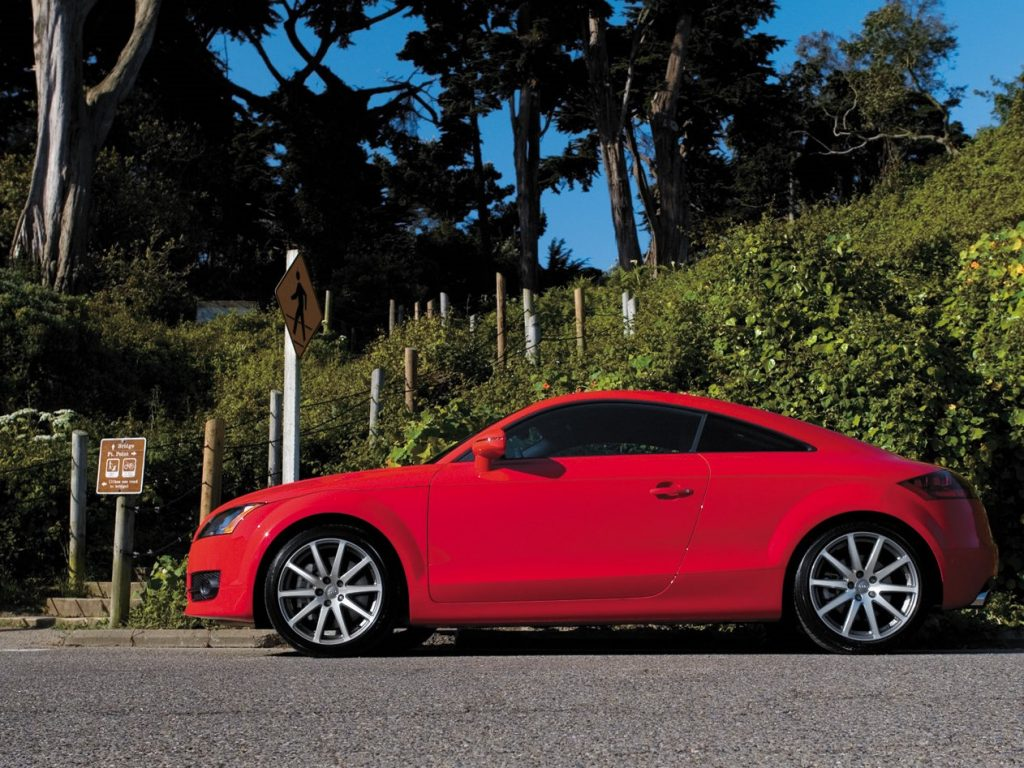 A red Audi sports car sits at an intersection.