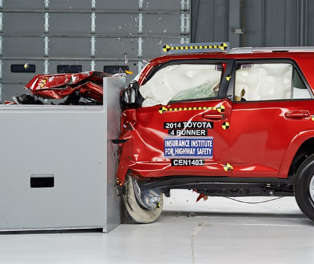 A red 2014 Toyota 4Runner SUV getting crash tested for safety
