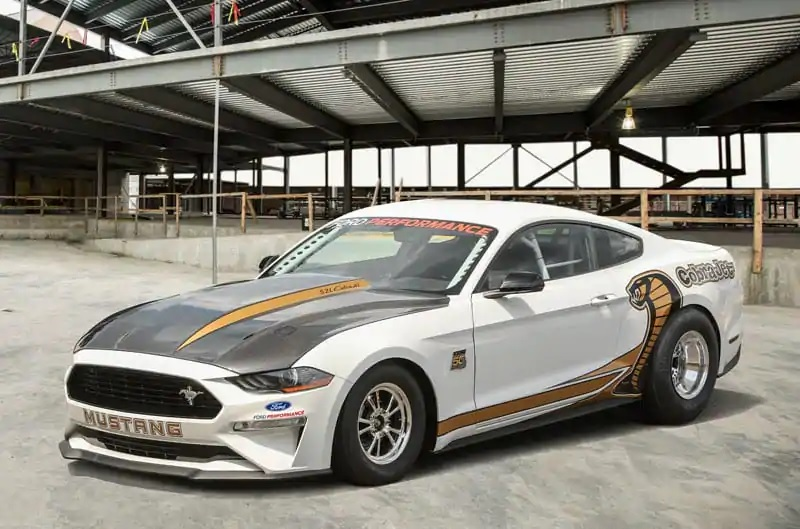 A black-hooded white-and-gold 2018 Ford Mustang Cobra Jet 50th Anniversary Edition in a factory