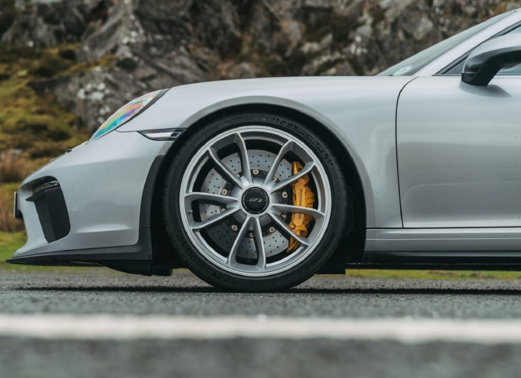 A silver 2018 Porsche 911 GT3 and its drilled brake rotors with yellow calipers