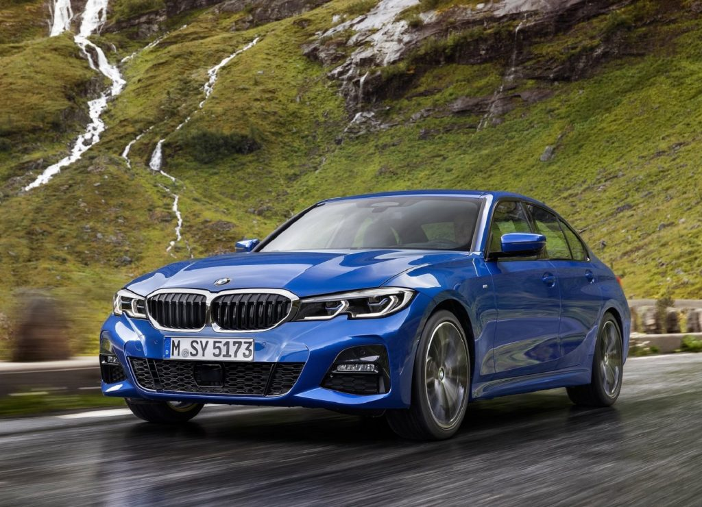 a blue 3 Series at speed on a scenic mountain road.