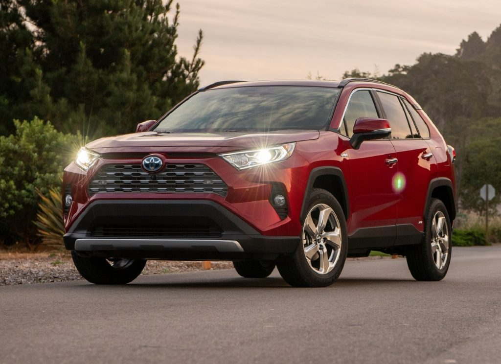 A red 2019 Toyota RAV4 Hybrid at sunset with its lights on