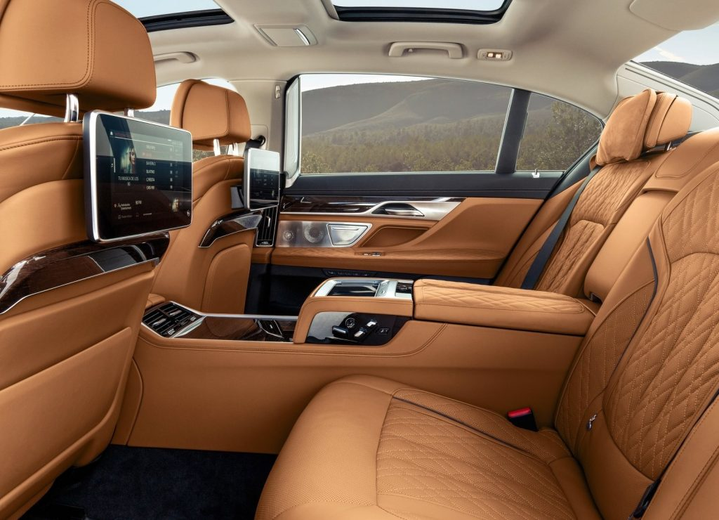The tan-leather-upholstered rear seats with digital displays of a 2020 BMW 7 Series