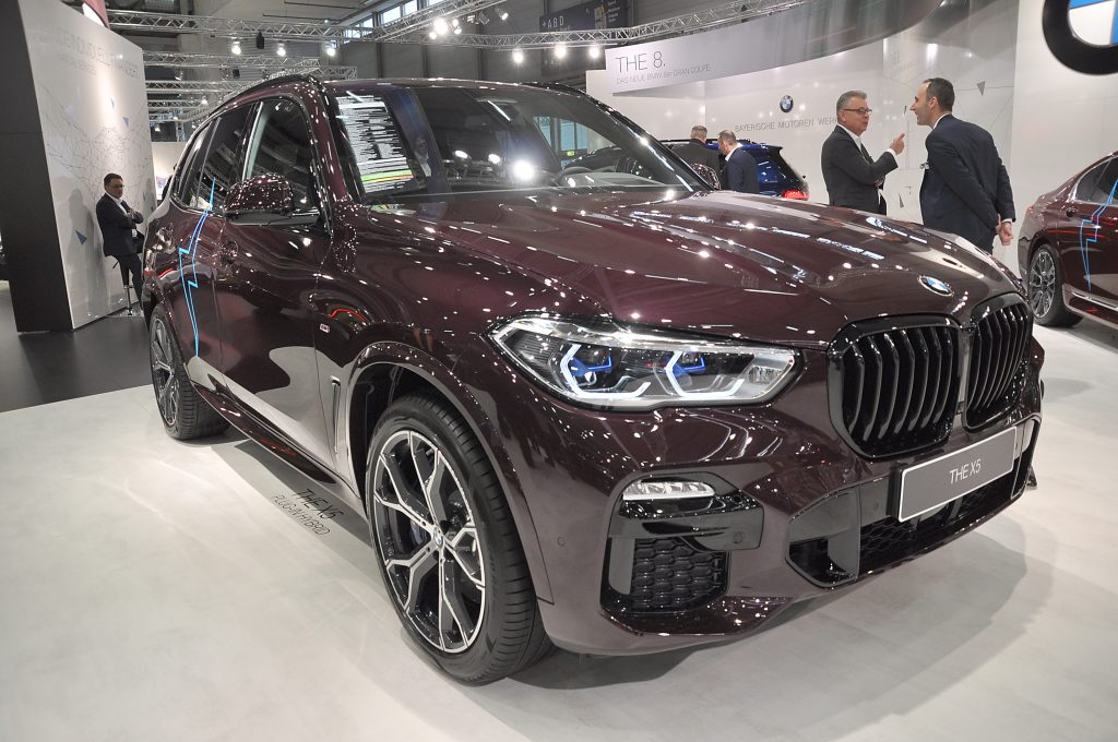 A maroon BMW X5 on display at an auto show