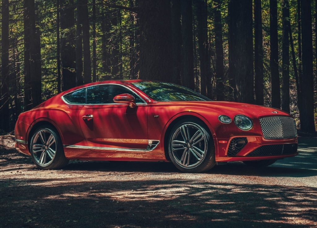 An orange-red 2020 Bentley Continental GT V8 in the forest