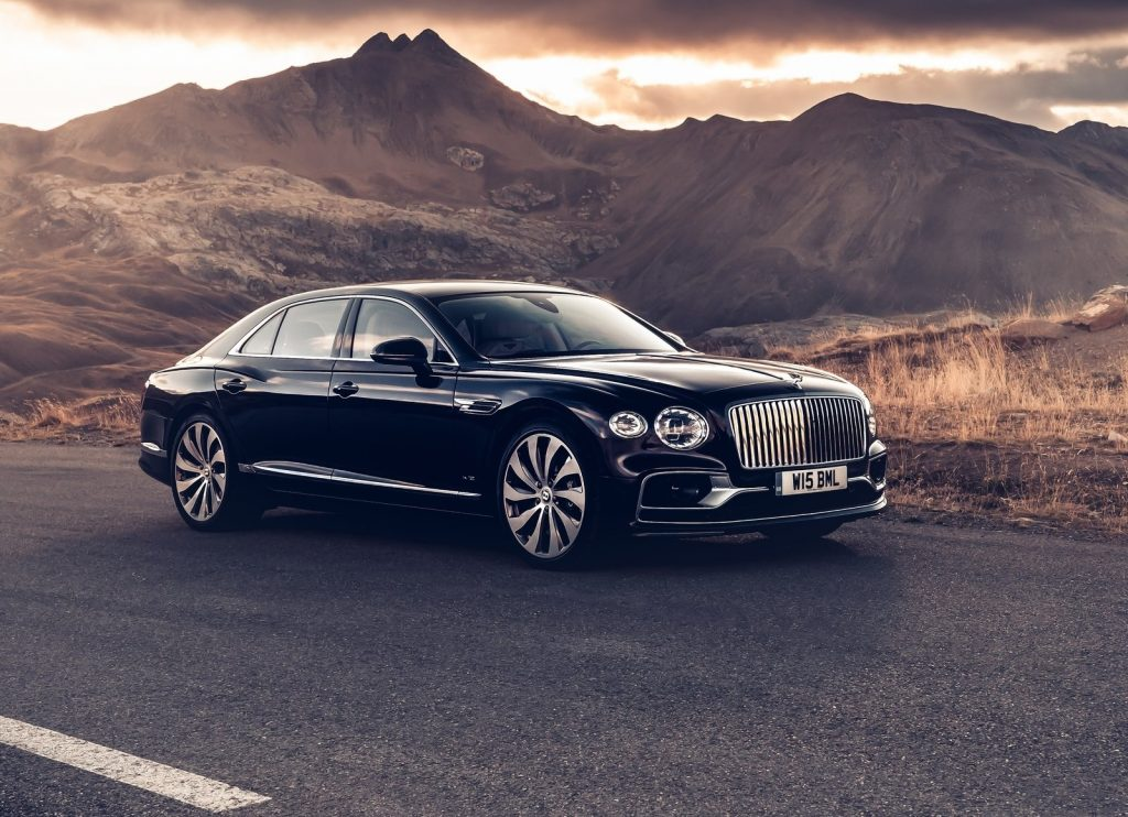 A black 2020 Bentley Flying Spur on a desert road with sunlit mountains behind it