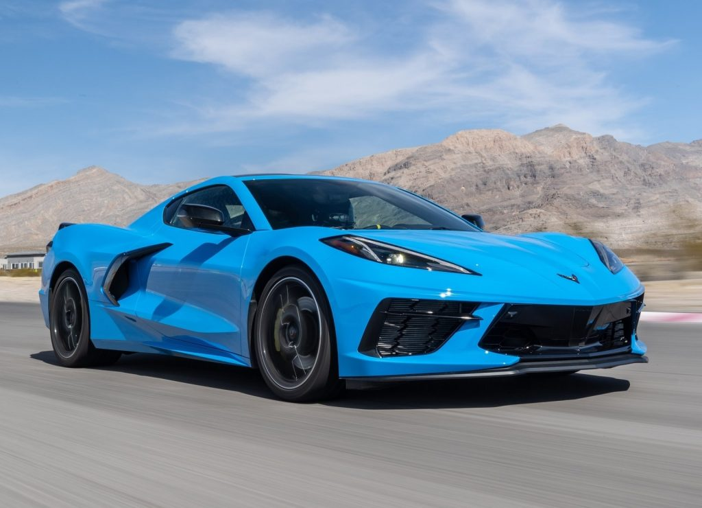A blue 2020 Chevrolet Corvette C8 Stingray races around a desert racetrack, exemplifying the reasons for its MotorTrend car of the year award