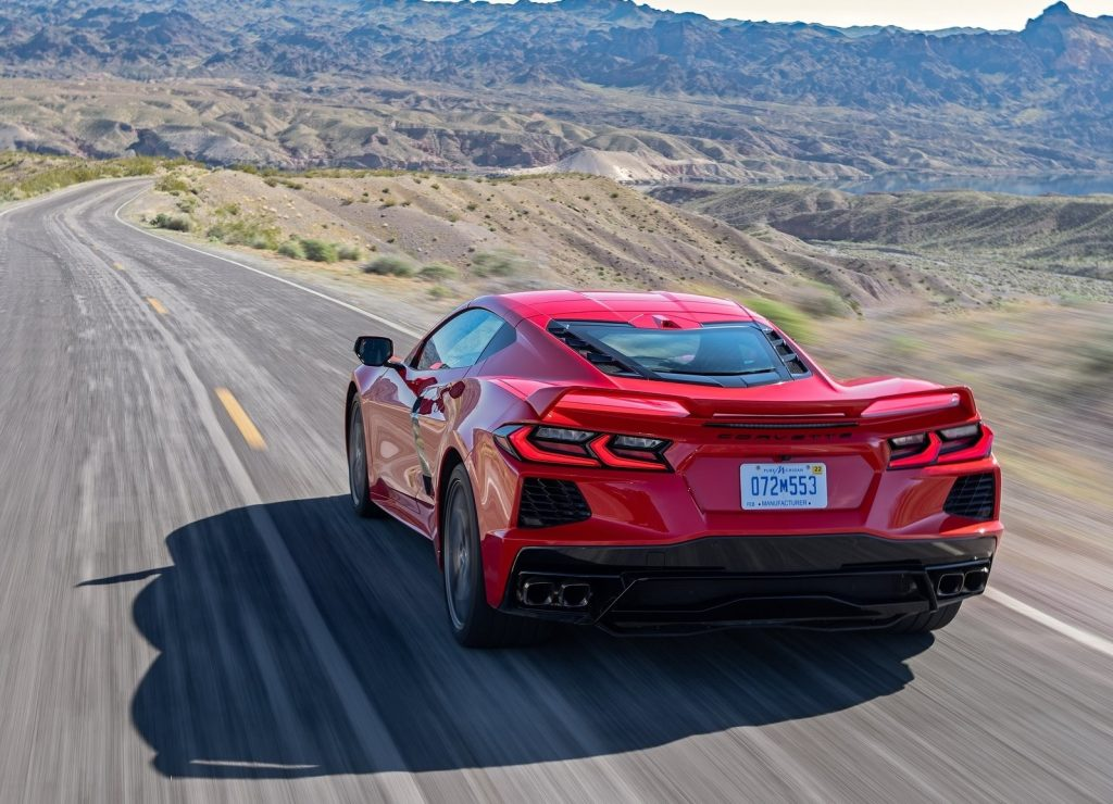 A red 2020 Chevrolet Corvette C8 Stingray races down a mountain road in the desert