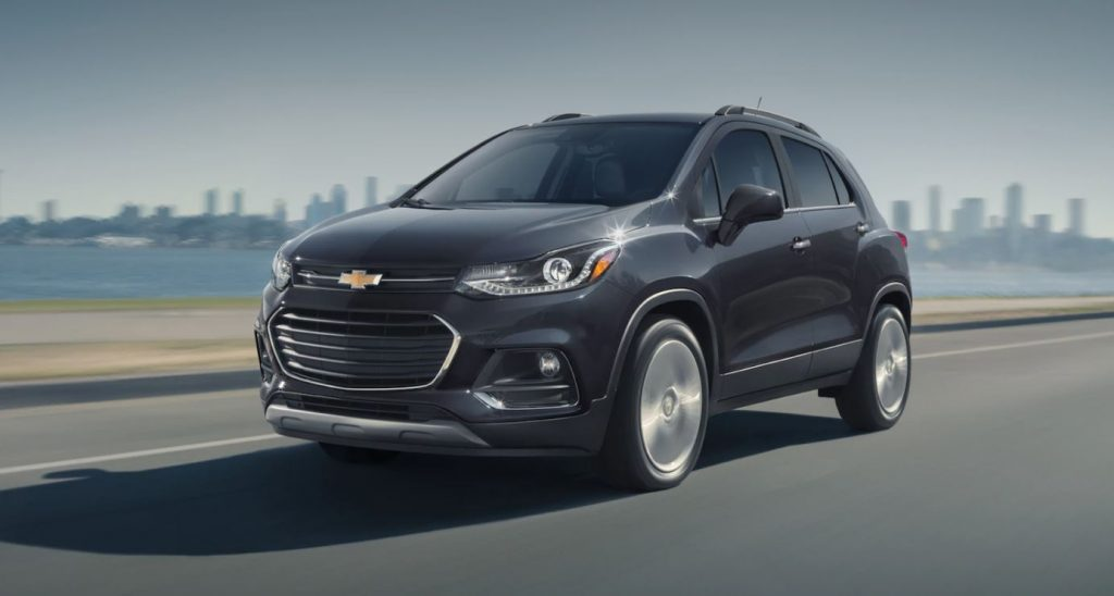 A black Chevrolet Trax SUV drives by a cityscape.