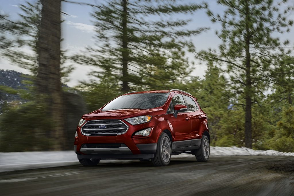 A red 2020 Ford EcoSport Titanium drives through a snowy forest