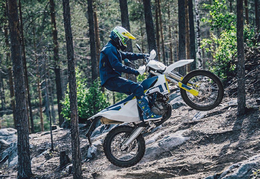 A rider jumps a white 2020 Husqvarna 701 Enduro through a forest