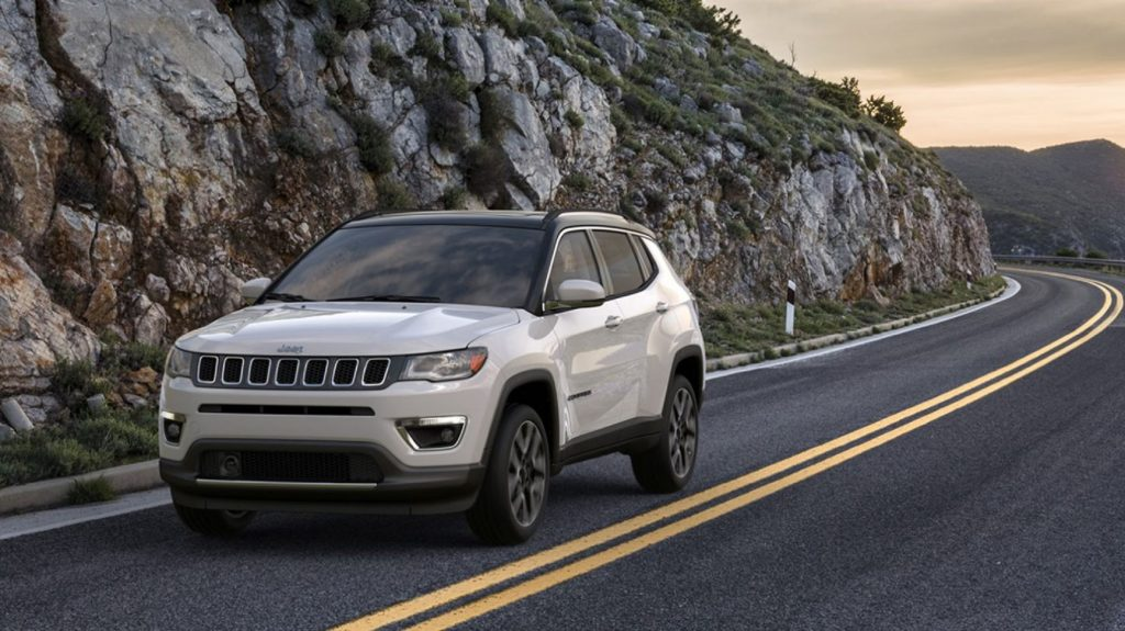 A white 2020 Jeep Compass drives next to a rocky hill