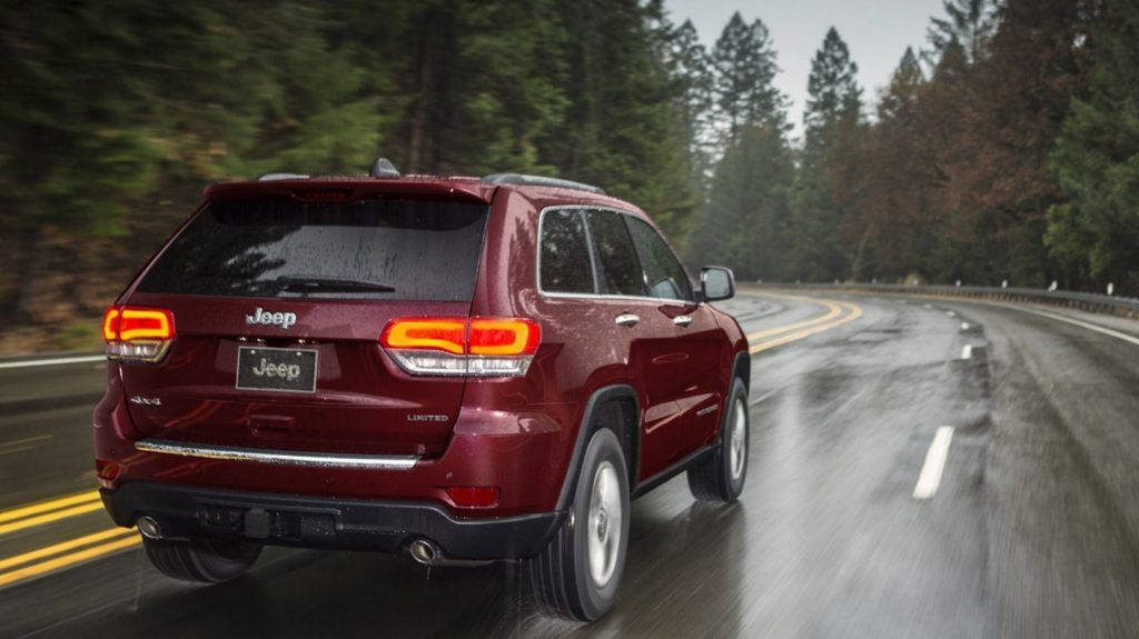The rear view of a red 2020 Jeep Grand Cherokee Limited driving through a rainy forest