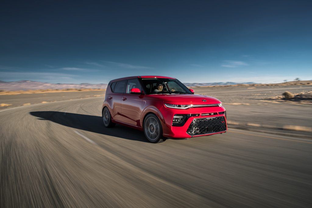 2020 Kia Soul GT-Line in inferno red driving on a track with a blue sky
