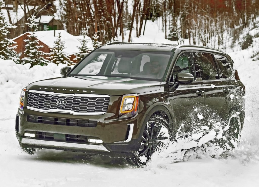 A green 2020 Kia Telluride drives through the snow