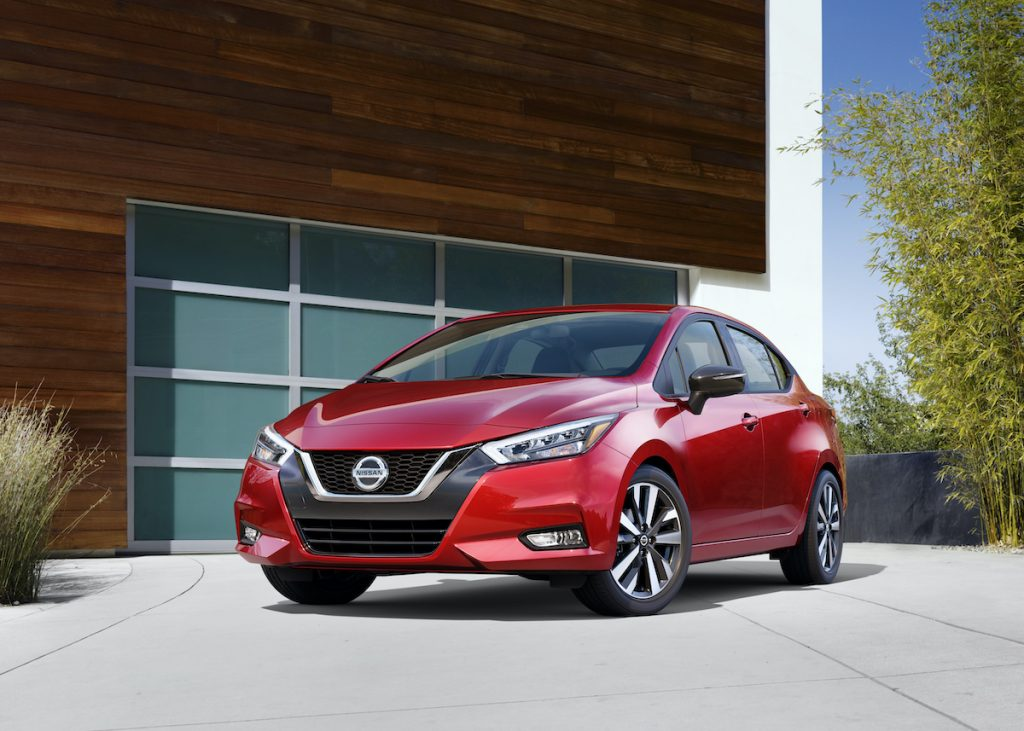 2020 Nissan Versa parked outside of a glass panel garage