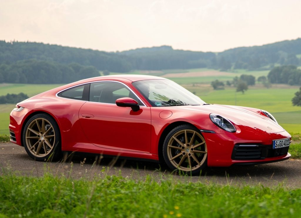A red 2020 Porsche 911 Carrera amongst rolling green hills