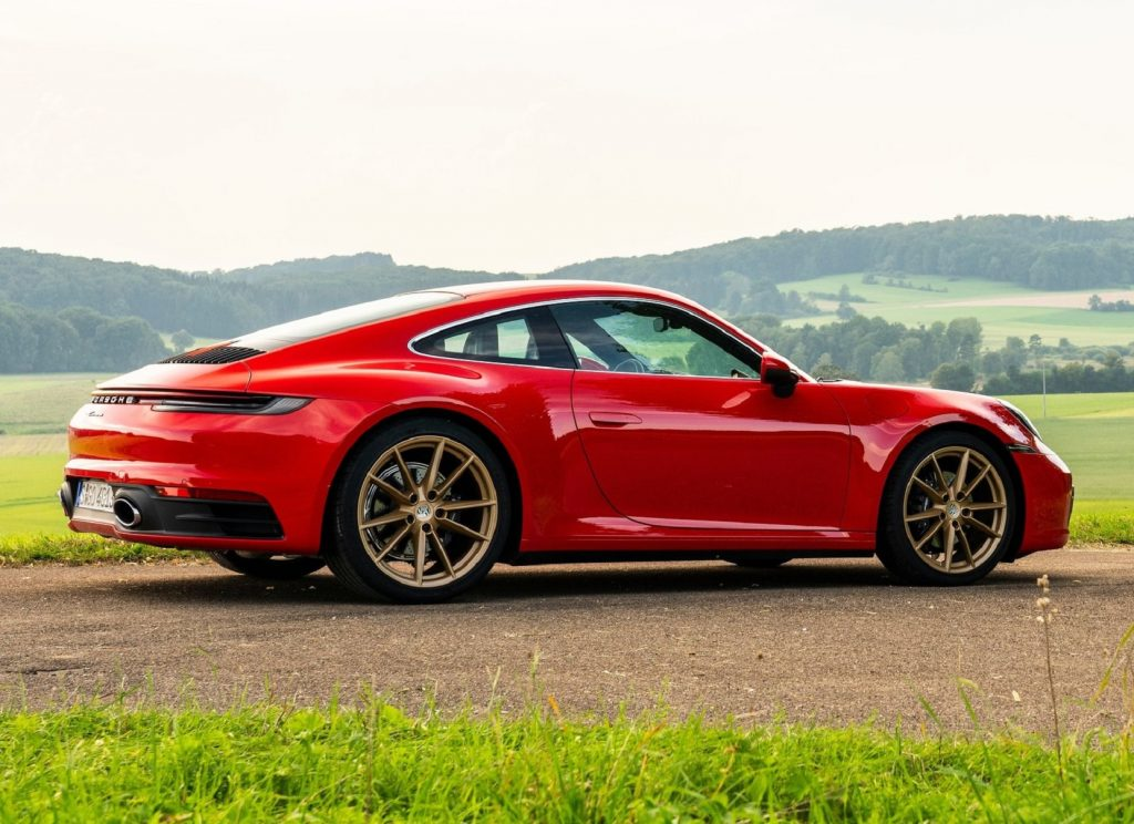 The rear 3/4 view of a red 2020 Porsche 911 Carrera among rolling green hills