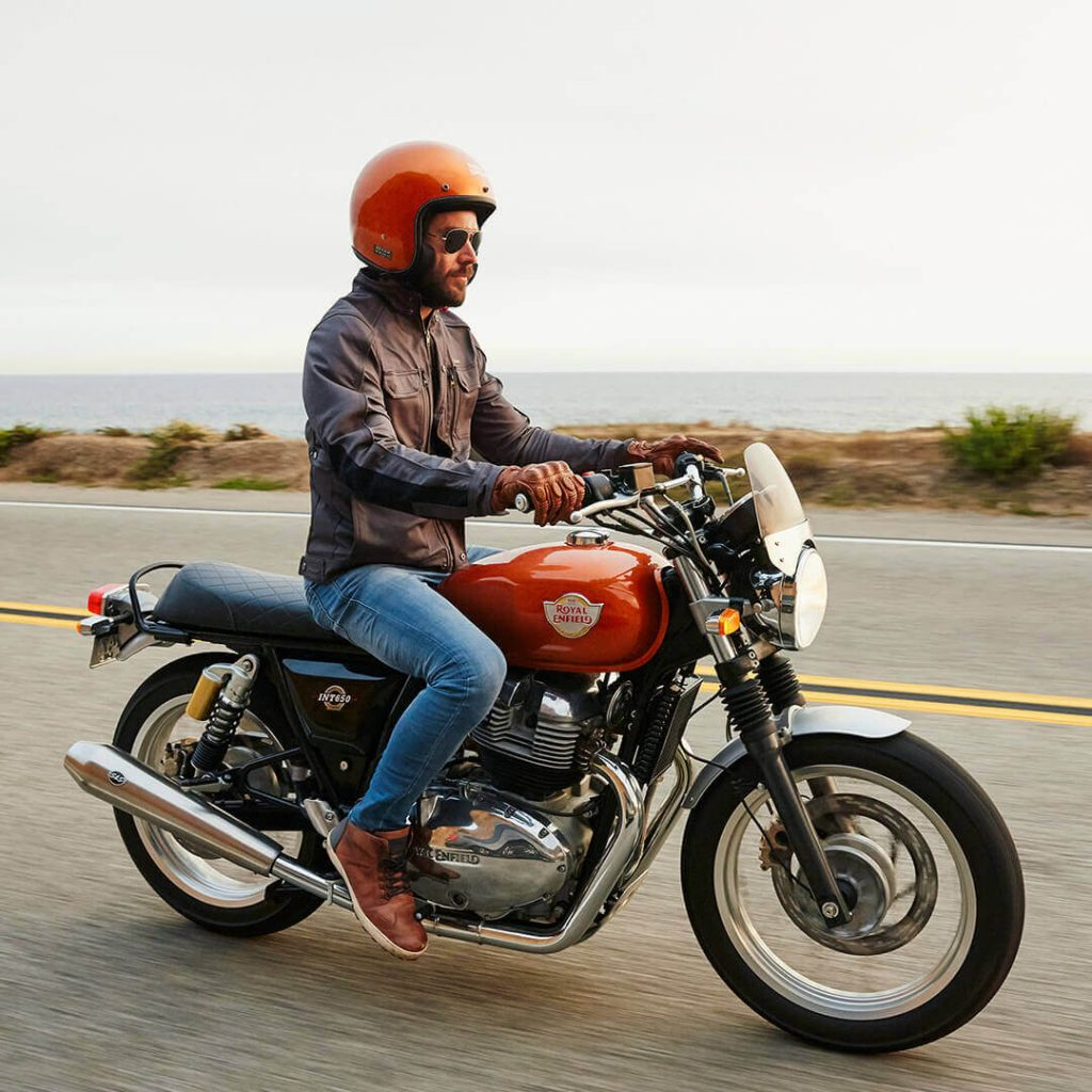 An orange-helmeted rider on an orange 2020 Royal Enfield Interceptor 650