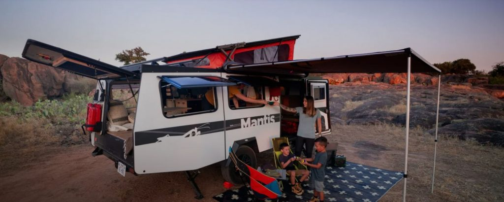 A white trailer with the pop-up extended sits on a trial with a family sitting under the exterior awning.
