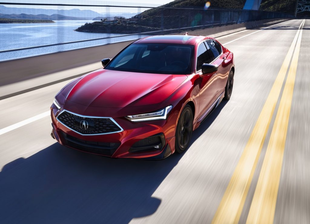 A red 2021 Acura TLX drives on a road over a body of water