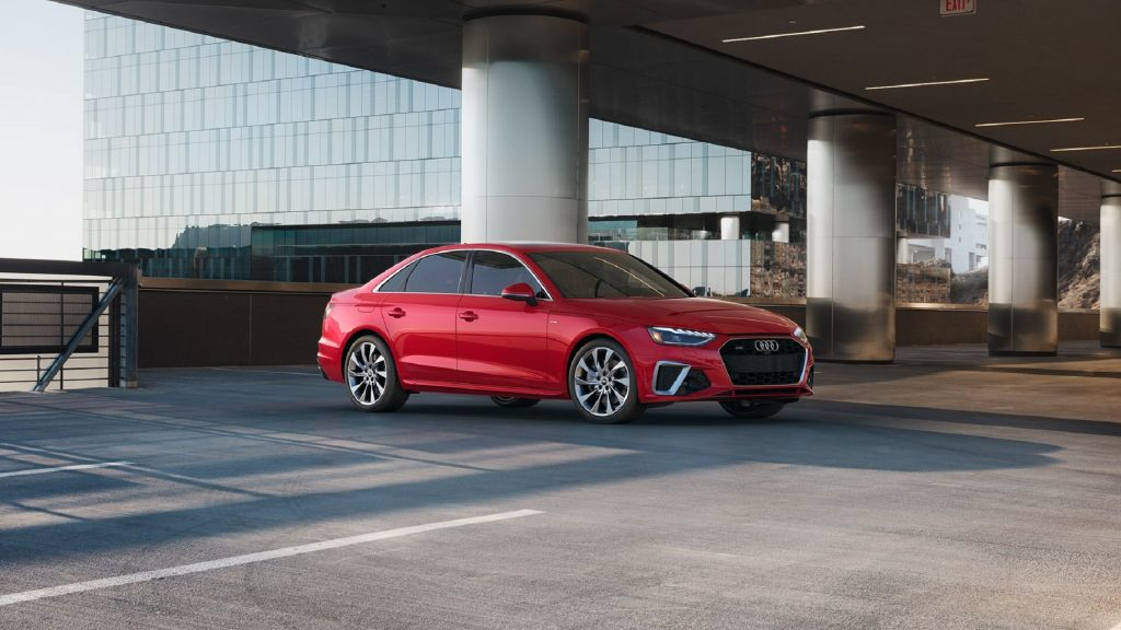 A red 2021 Audi A4 parked in front of a modern upscale hotel