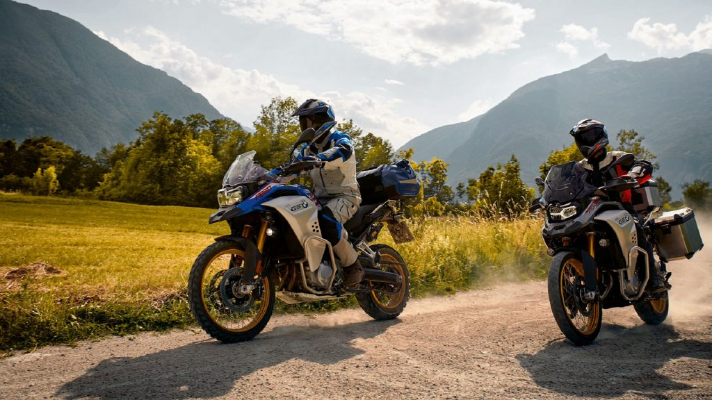 A blue-and-silver and a red-and-silver 2021 BMW F 850 GS Adventure on a mountain gravel trail