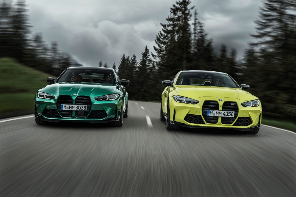 A green 2021 BMW M3 Competition and yellow BMW M4 Competition drive down a forested mountain road