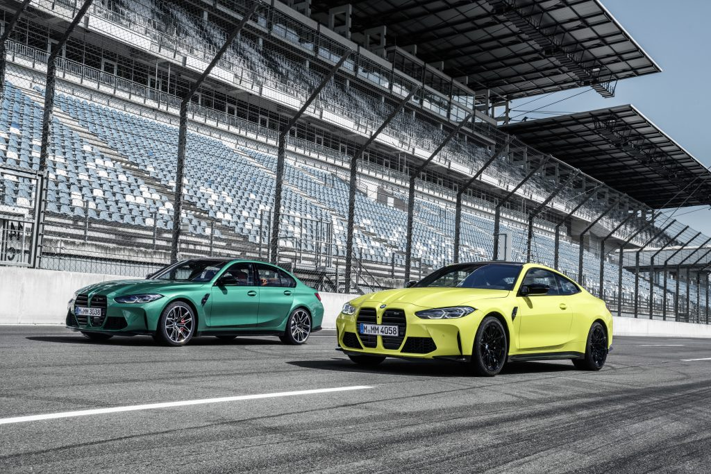 A green 2021 BMW M3 and yellow M3 on a racetrack