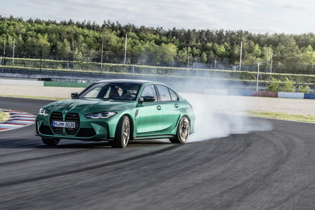 The front 3/4 view of a green 2021 M3 sliding around a racetrack