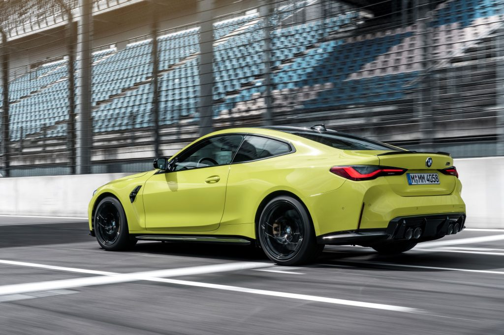 The rear 3/4 view of a yellow 2021 BMW M4 on a racetrack