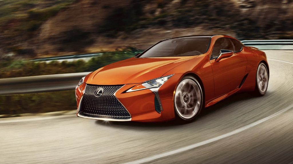 2021 lexus LC 500h in a gorgeous orange carving corners on a mountain road