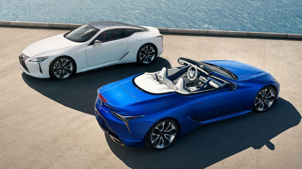 A white 2021 Lexus LC500 Coupe above a blue 2021 Lexus LC500 Convertible parked by the sea