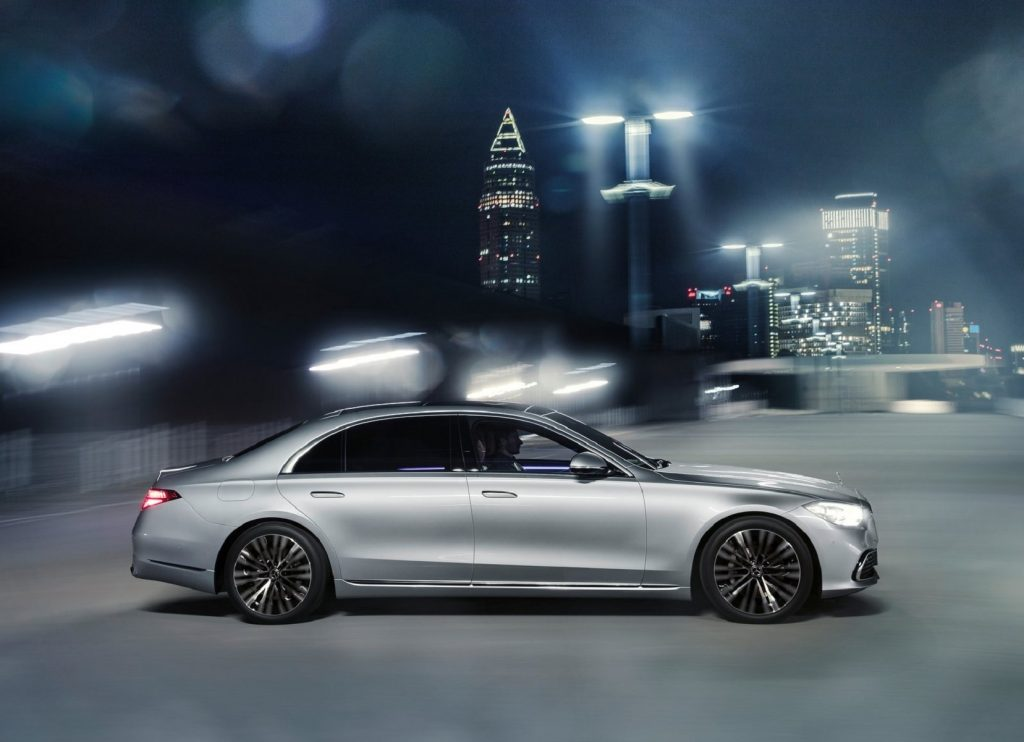 A silver 2021 Mercedes S-Class drives through a bright-lit night city