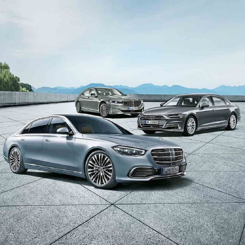 A light-blue 20201 Mercedes S-Class in front of a silver 2020 Audi A8 L in front of a gray 2020 BMW 7 Series