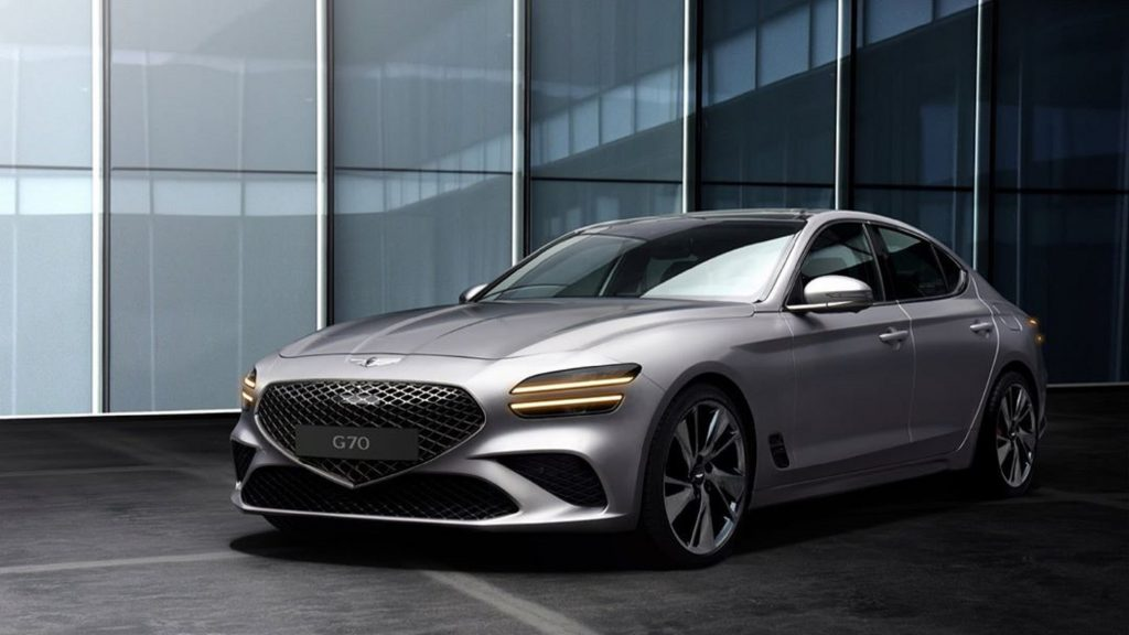A silver 2022 Genesis G70 in front of some glass windows