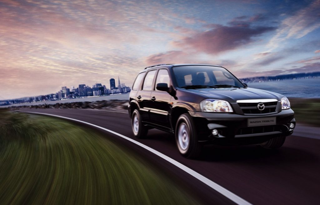 a black 2005 Mazda Tribute SUV driving at speed on a scenic road with an urban view
