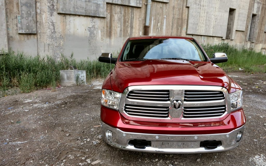 A red Ram 1500 pickup parked in front of a brown shed.