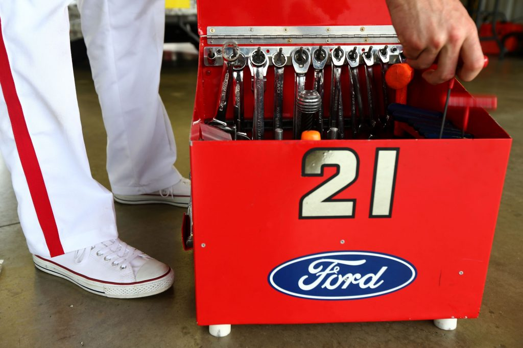 A white-suited NASCAR mechanic reached into their red open toolbox