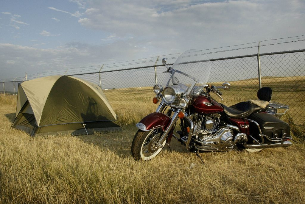 A red cruiser motorcycle parked next to a green camping tent in a grassy field