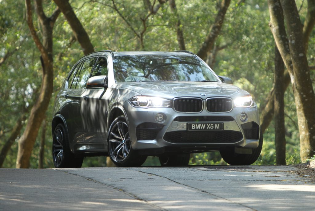 A BMW X5 parked on the street for a photo