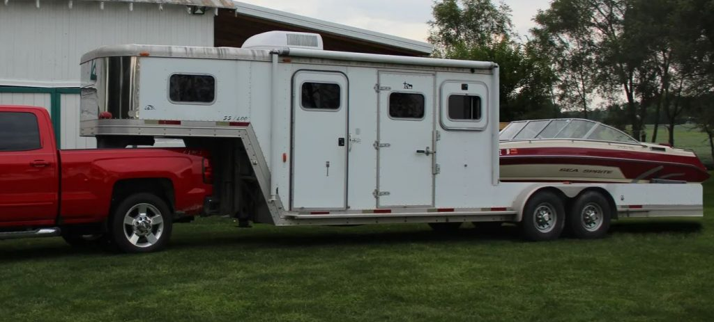 A white horse trailer has been converted to carry a boat in the rear.
