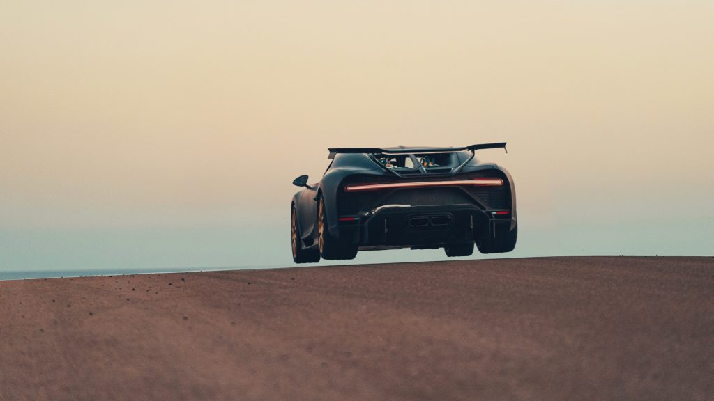 The silhouette of the rear of a car getting airborne cresting a small hill.