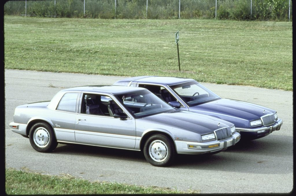Gray 1988 Buick Rivera model parked next to a dark blue 1989 Buick Rivera model which is 11 inches longer.