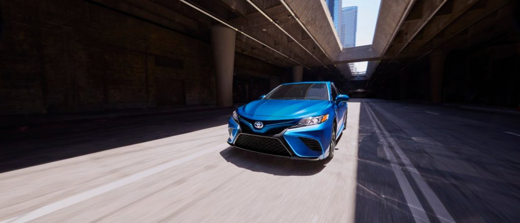 A bright blue 2020 Camry Hybrid whizzing through city streets.