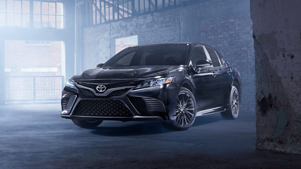 a nightshade edition Toyota Camry parked in an industrial brick warehouse garage